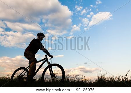 Mountain biker riding on bike in spring inspirational sunset silhouette. Man cycling MTB on enduro inspiring trail. Sport fitness motivation and inspiration.