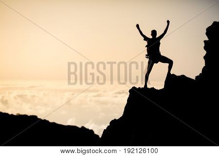 Man successful hiking climbing silhouette in mountains motivation and inspiration in beautiful sunset. Climber arms up outstretched on mountain top looking at inspiring landscape.