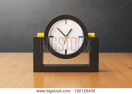 Table clock of black and yellow plastic on a light wooden table. White clock face with black yellow and red arrows covered by glass. The background is gray plastered wall. 3D illustration.