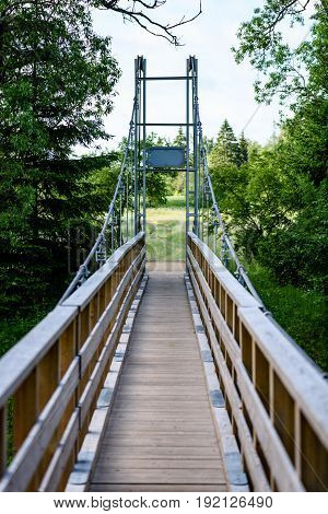 Diminishing Perspective Of Metal Suspension Footbridge Over River