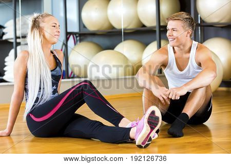Full length of smiling young man and woman sitting in gym