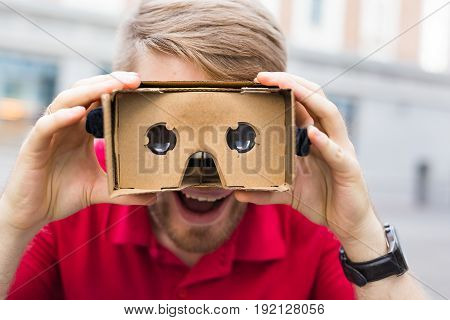 Close-up of funny man using cardboard virtual reality goggle outdoors.