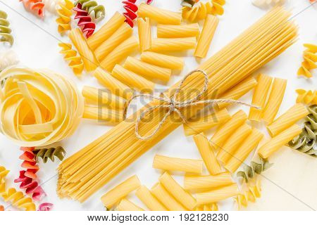 Assortment of different shape italian pastas on white background top view.