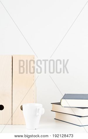 White office desk with books cup and folders - copy space - study or workplace background mock up