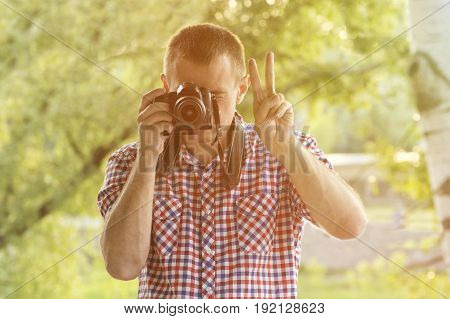 Photographer takes pictures against the background of greenery. Front view. Victory hand