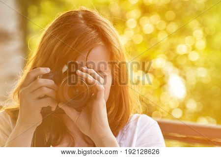 Girl photographer takes pictures against the background of greenery. Front view