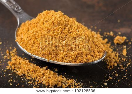 Spoon filled with spices for the preparation of roast on rusty background