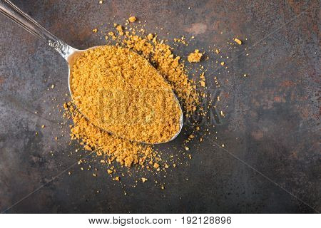 Spoon filled with spices for the preparation of roast on rusty background with copy space
