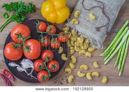 Concept of italian cuisine, vegetarian and healthy food. Ingredients for italian food - uncooked pasta and vegetables, different varieties of tomatoes, garlic, asparagus, bell pepper on wooden background. Top view