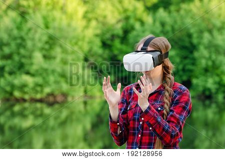 Girl in virtual reality glasses is holding her hands in front of her against the background of greenery