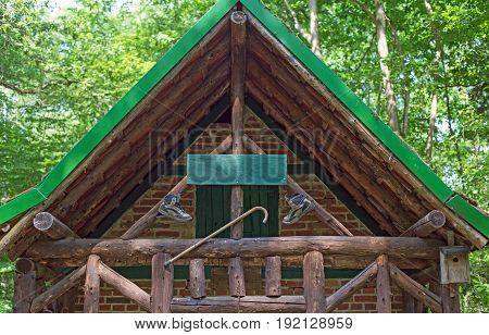 A wooden cabin with walking boots and walking stick in a forest