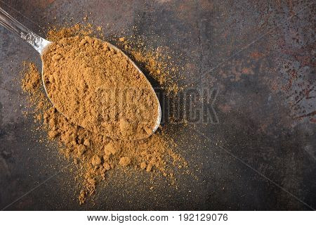 Spoon filled with cinnamon powder on rusty background with copy space