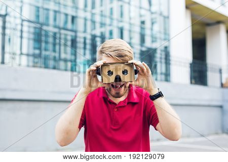 Funny man using cardboard virtual reality goggle outdoors.