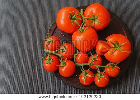 Different varieties of fresh red ripe organik tomatoes with water drops on branches, dark linen napkin. Close-up. Selective focus. Top view. Concept of vegetarian and healthy food. Copy space