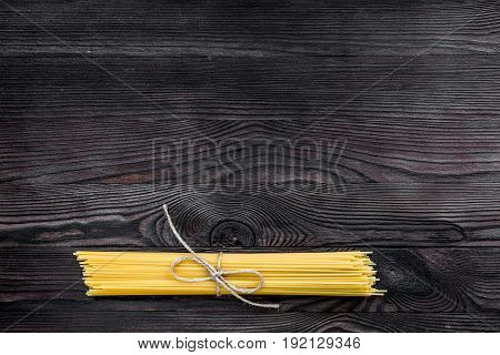 Bunch of spaghetti tied with rope on grey wooden table top view copyspace.