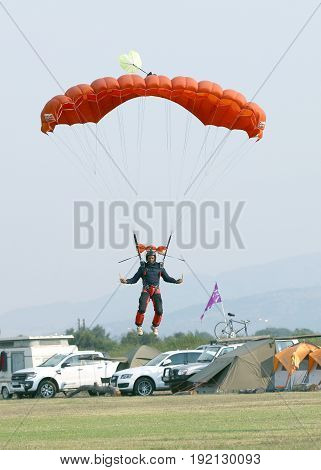 Black African Male Skydiver Coming In For Landing On Grass With Open Bright Colourful Parachute.