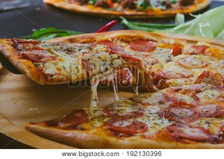 Hot pizza slice with melting cheese on a rustic wooden table.