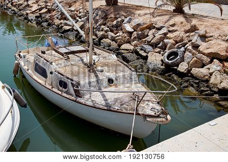 The old dirty boat in the port. Marina de las Dunas, Guardamar del Segura, Alicante, Spain