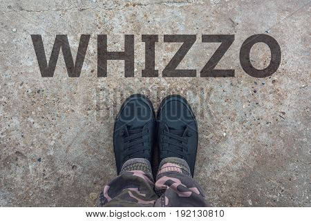 Whizzo british slang for superb and excellent with brand new modern tennis shoes on concrete sidewalk
