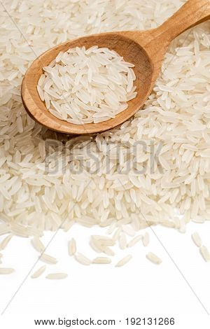 Parboiled rice with wooden spoon on white background. Close up. Copy space high resolution product. Healthy food concept