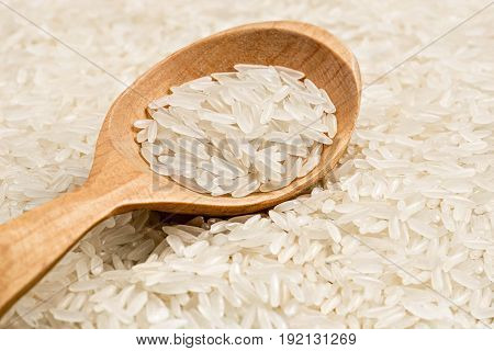 Wooden spoon on background of long parboiled rice. Close up. High resolution product. Healthy food concept