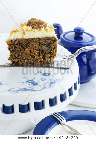 homemade carrot cake with walnuts on a pretty cake stand with sliver wear,  copy space in foreground and background image in blue and white colors. poster