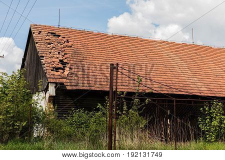 Broken brick bags on the roof of a cottage. Damaged roof.