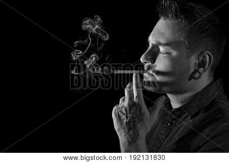 Black and white portrait of young, attractive, tattooed man with ear tunnel and facial hair smoking a cigarette