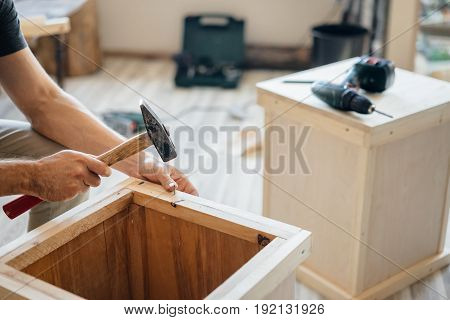 Male hand carpenter with a hammer. A man clogs small nails into a wooden structure on the floor. Handmade master.