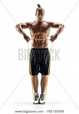 Muscular man performs exercises using a resistance band. Photo of young male isolated on white background. Strength and motivation. Full length