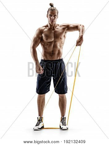 Man with beautiful athletic body performs exercises using a resistance band. Photo of muscular male isolated on white background. Strength and motivation. Full length