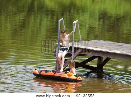 Two Boys Having Fun with Inflatable Rubber Boat in Summer