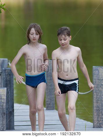Two Boys Walking on Jetty in Summer