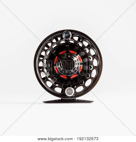 Fly Reel black and red on white background. Fly reel for fly fishing. Fly reel close-up.