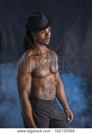 Attractive muscular shirtless young black man with grey fedora hat, on dark background