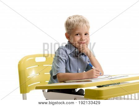 Portrait of happy smiling little boy sitting at the desk and thinking