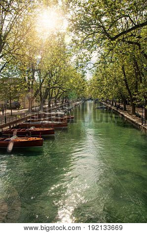 Large canal with boats and trees in the city center of historic Annecy. Located in the Haute-Savoie department, south-eastern France. Retouched photo