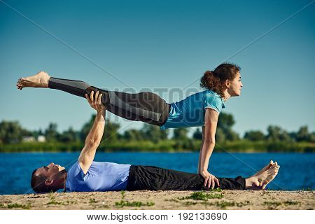 Young acroyoguis practicing Chaturanga Dandasana pose outdoors