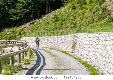 Attractive female cyclist tackling a steep road. Enjoying Madonna di Campiglio, Italy.