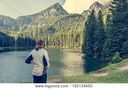 Attractive brunette enjoying lake view with surrounding forest. Lago di valagola near Madonna di Campiglio, Italy.