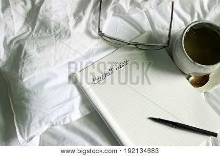 White bedding with notebook and text