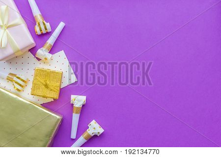 Birthday concept with gifts, greeting cards and party whistles on violet background top view copyspace.