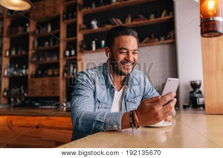 Happy young man sitting at coffee shot with earphones making video call to friend. Caucasian male having video chat on smart phone at cafe.