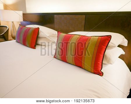 Sideview of Red Pillows and White Pillows on White and Comfort Bed with Light from Bedside Lamp.
