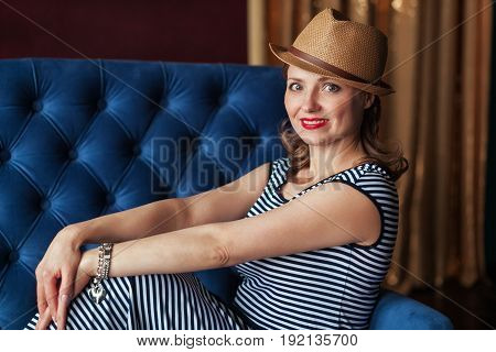Laughing woman in brown hat sitting in blue armchair