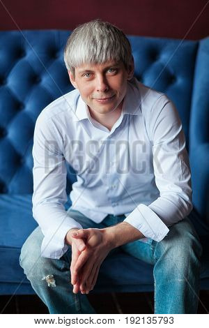 Grey haired Man sitting in blue armchair