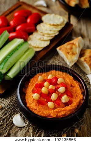 Red Bell pepper hummus with vegetables on a wood background