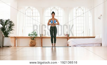 Full length portrait of fit young woman standing with her hands joined at home. Fitness female meditating indoors.