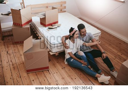 Young couple moving in new house and taking self portrait with smart phone. Young man and woman sitting on floor making selfie with mobile phone.