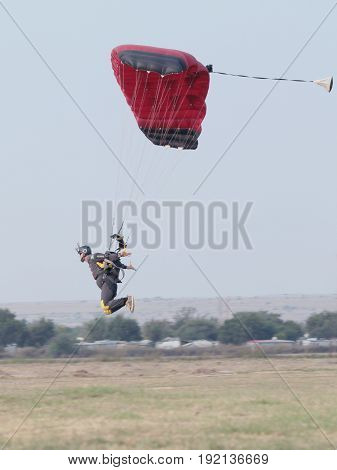 Male Skydiver Coming In For Extra Fast Landing On Grass With Open Brightly Coloured Parachute.